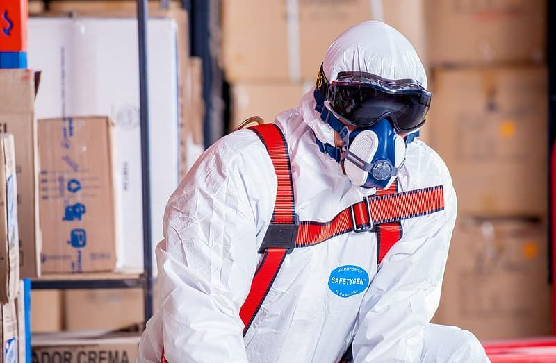 photo-of-man-in-white-safety-suit-near-cardboard-boxes